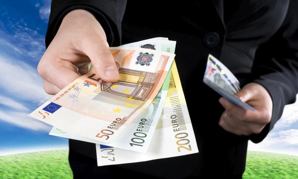 Ruka podávající euro bankovky
