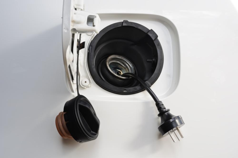 Otevřená nádrž auta se šňůrou od elektriky